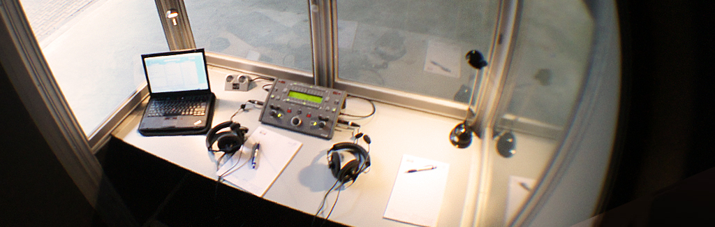 Dolmetschtechnik - ein Blick in die Dolmetschkabine mit Dolmetschpult und Kopfhörer