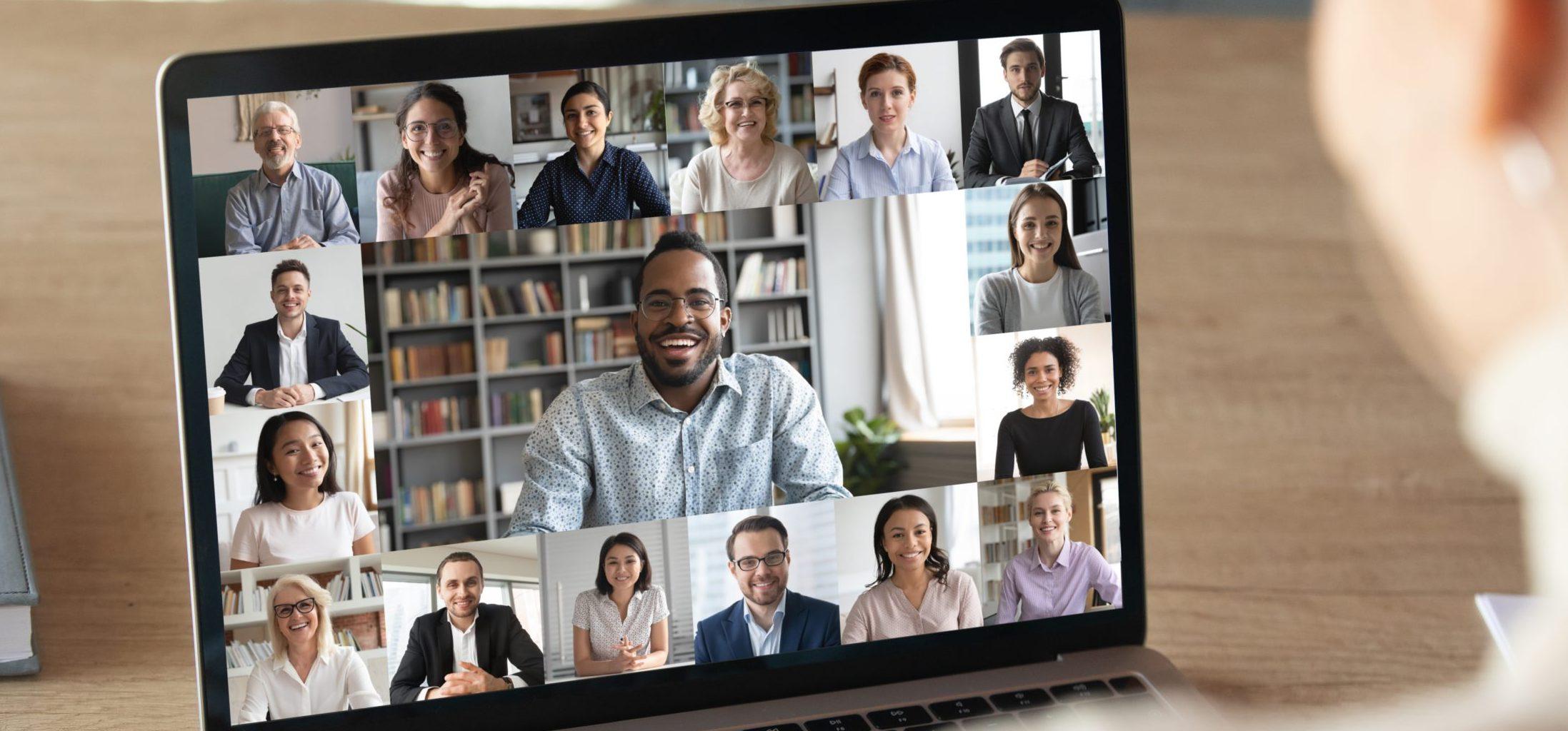 Eine Managerin nimmt am Laptop an einer Videokonferenz teil. Man sieht viele unterschiedliche Teilnehmende auf ihrem Bildschirm.